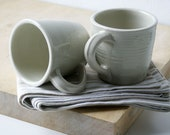Set of two simple curved stoneware mugs - glazed in simply clay