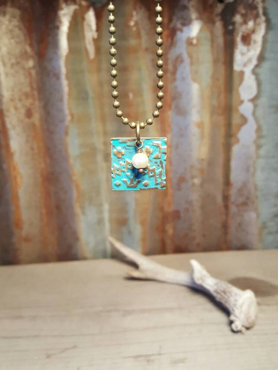 Embossed brass metal necklace with pearl accent. Turquoise embossed metal necklace.