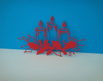Cut out of 3 candles on red Holly leaves