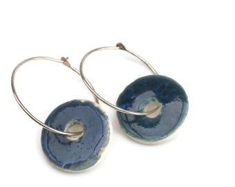 Dark blue glazed ceramic hoop earring. Unique ceramic jewellery. Retro rustic blue glaze on a white ceramic bead. Handmade ceramic jewellery
