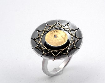 The web, A statement round gold and oxidized silver geometric ring with a small diamond and a distinctive design that refers to Halloween.