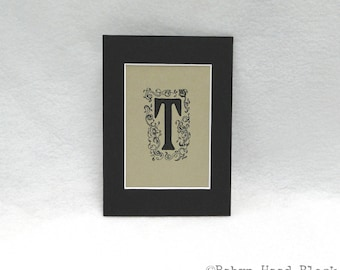 Letter T in 5 X 7 mat hand embellished print from letterpress block black on gold