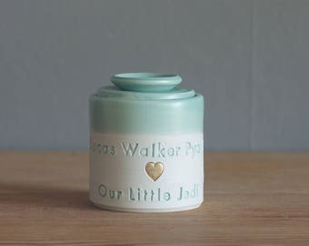 custom infant urn with ceramic lid. straight shape with custom name and date. modern urn for ashes. infant urn. green with gold shown