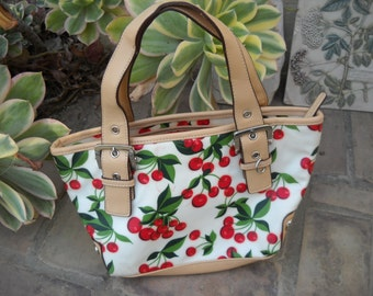 XOXO Cherry fun purse, Durable vinyl, finely crafted, Zips closed with interior zip section as well. 11.5 wide and 6.5 deep, big enough