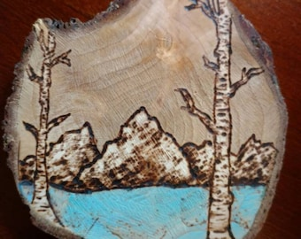Wood burned mountain scenery with birch trees