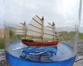 Ship in a bottle, Chinese Junk, Sampan, sailing on a blue sea