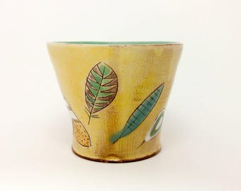 Yellow feather themed Earthenware Tumbler. Wheel thrown and altered, food safe cup, made by Kaitlyn Brennan/ Brennan pottery