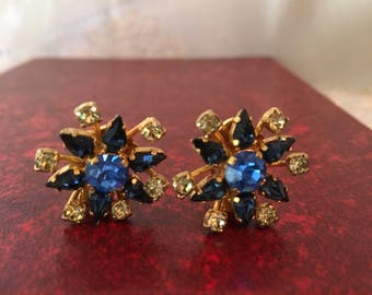 Beautiful clear rhinestones encircling seven vibrant blue stones. Clip on Earrings marked AUSTRIA.