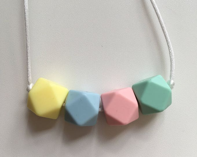 Teething necklace in pale yellow, powder blue, mint green, pale pink; made from BPA free chewable silicone hexagon beads by Little Gnashers