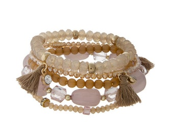 Tan beaded stretch bracelet set with tassels and gold tone hardware