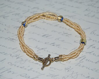 Wire Wrapped Four Strands Gold Beige Bracelet with Golden Blue Lampwork Glass.