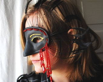 Asymmetrical black half mask with red bead fringe gold glitter and feathers