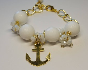White bracelet with a gold anchor.