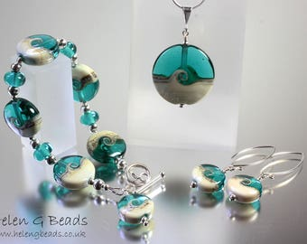 Jewellery set in Teal Green and cream. Includes 1 bracelet, 1 pendant on a chain and 1 pair of earrings.