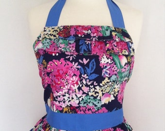 Retro apron with ruffles, vintage style pink floral pattern on a blue fabric.