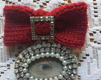 Red knitted bow, lover's eye brooch with diamanté