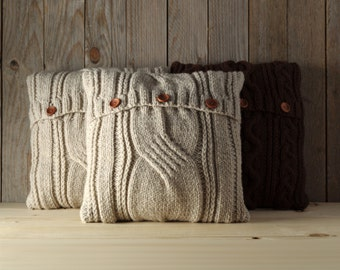 Light beige cable knit pillow cover with 3 wooden buttons.