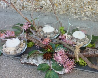 Natural candle on slate with artificial flowers