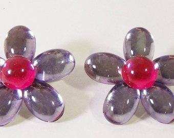 Five petal lavender flowers with magenta centers.  Reflective stones.