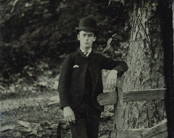 Tintype of well dressed man in hat, outdoor pose.