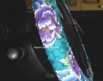 Steering wheel cover with pretty purple and turquoise flowers on teal green fabric. Metallic gold trim.