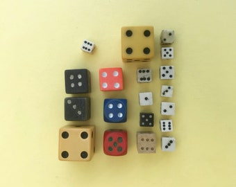 A collection of vintage dices, 19 dice from 18mm to 6mm. Ochre, red, blue, black, pink and white dices, wooden, bakelite and