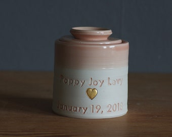 custom urn. gold infilled stamp with ceramic lid, straight shaped urn, heart stamp. modern simple urn for ashes. peach pink urn with gold.