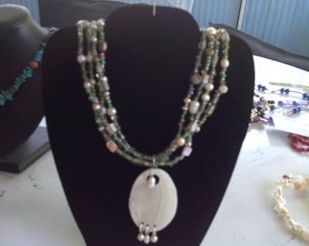 Four strand necklace of natural shell,seed beads and freshwater pearls.