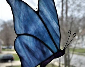 Stained glass butterfly suncatcher with streaky blue and purple wings and a purple body, 5 x 7
