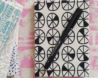 Pocket sized hardback sketchbook in screen printed fabric by Lucie Summers, Spokes design in Coal black