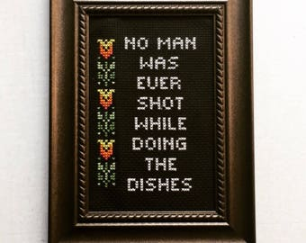 No man was ever shot while doing the dishes. Finished and framed cross stitch.
