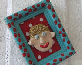 Quirky hand built clay face ornament in vintage wooden frame recycled repainted with polka dots
