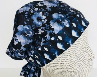 Tie Back Scrub Cap scrub hat featuring a dark blue material with flowers in a gray blue color with a coordinating band 2t