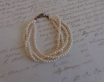 Bracelet  Four strand faux pearl bracelet.  Tiny pearls and lobster clasp