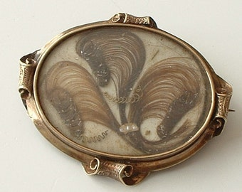 Victorian mourning brooch with scroll decorated frame
