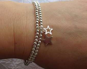 Two Sterling silver stacking bracelets with open and solid star charms