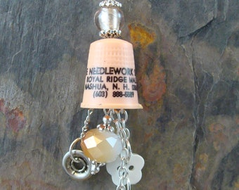 Vintage advertising thimble - The Needlework Shop, Nashua, NH with beads, button, snap, yarn & silver plated accents