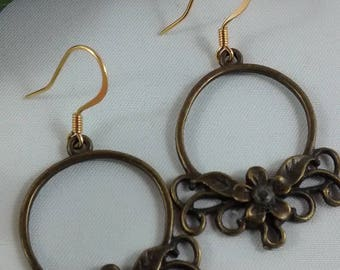 Hoop earrings with clear sapphires set in a floral setting