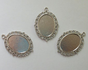 12 silver tone pendants with 25x18 glue in settings