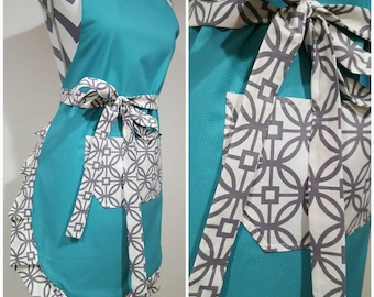 Adult apron. Woman's apron. Teal on main bodice with gray and white design on pocket, ties and frills.