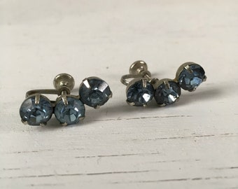 Blue vintage rhinestone earrings both curved in the same direction
