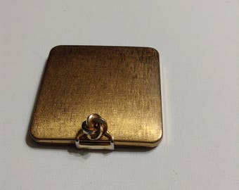 Volupté square gold tone compact with a love knot lid lock closure, vintage 1940s.