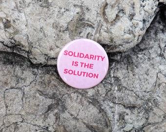 Badge à épingle rose | Pin's | Slogan Solidarity is the Solution | Imprimé à Paris| Made in France | Marque française engagée