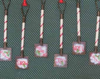 Set of six hand painted shovel Christmas ornaments with holiday words and pine boughs