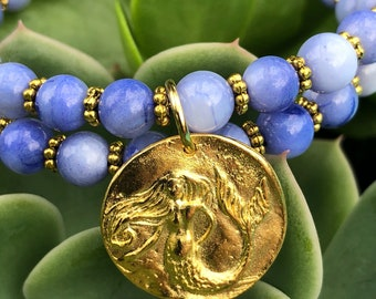Blue glass and antiqued gold accents with a mermaid charm