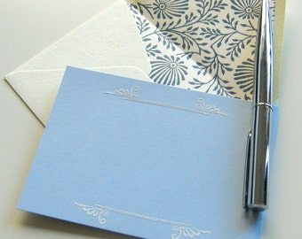 BLUE BRACKET CARDS - 4 baby blue flat cards with white scroll bracket motifs and hand lined floral motif envelopes in cream and navy