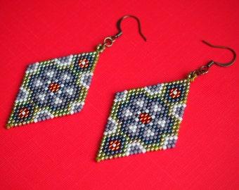 psychedelic peyote flower Delica seed bead earrings. brick stitch beadwork dangle earrings in purple, olive green, orange, and white.