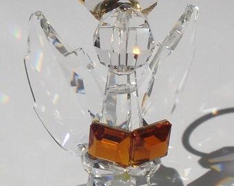 Crystal angel made with Swarovski crystal holding book