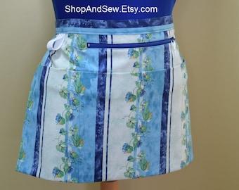 "Teacher half apron with 4 pockets, one has zipper for bills, 10"" tablet.  Blue lines / floral print.  Vendor, server, money, gardener apron"