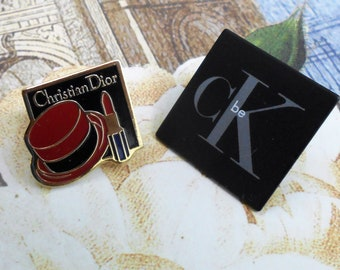 vintage Christian Dior and Calvin Klein pins, brooches, pinbacks. cK Be fragrance, Christian Dior Rouge lipstick promotional advertising.